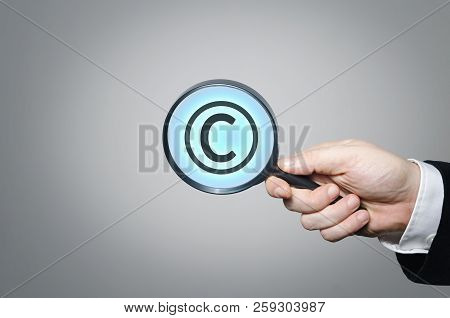 Copyright Symbol Under A Magnifying Glass. Conceptual Image Of Intellectual Property And Copyright.