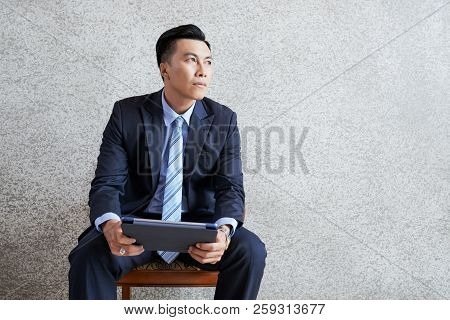 Adult Asian Man Sitting With Tablet In Armchair And Looking Away In Contemplation Against Gray Wall