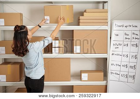 Office Worker Putting Parcel On The Shelf At Post Office