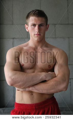 Young muscular man with crossed hands