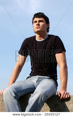 Sexy young man sitting on the stone blocks