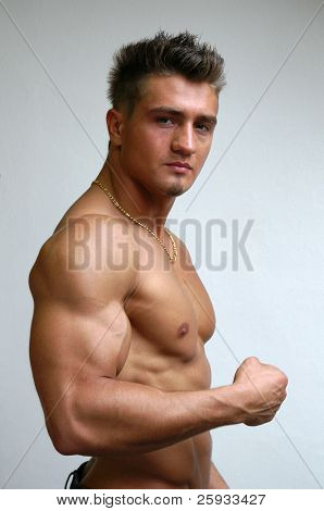 Muscular young model flexing biceps