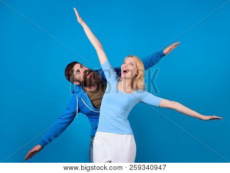 Holidays, Vacation, Love And Friendship. Smiling Couple Having Fun, Pretending To Be Flying. Dream,
