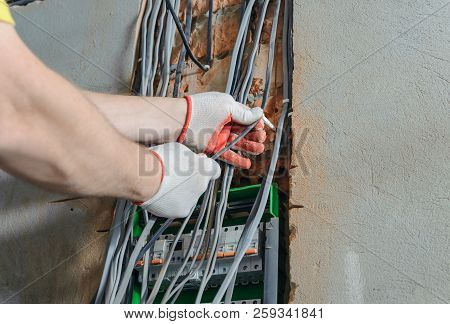 An Electrician Is Installing Electric Wires In A Switching Fuse Box.