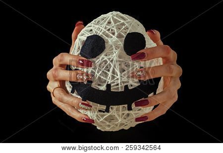 Halloween mummy in female hands isolated on black background. Spirit and supernatural. White face with spooky smiley and manicure with gems. Nail art concept. Holiday and party celebration. poster