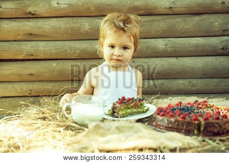 Cute Little Boy In White Pinafore Sits At Table Served With Fruit Cake And Cup Of Milk Outdoors On W