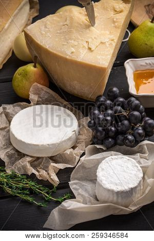 Parmesan And Goat Cheese With Pears, Grape And Honey On Dark Wooden Table