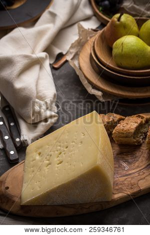 Slice Of Asolo Cheese On Wooden Plate With Pears And Bread On Dark Background
