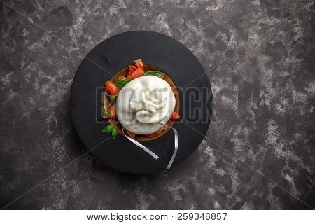 Whole Tied Italian Cheese Burrata On Small Wooden Plate Served With Fresh Tomatoes And Basil On Dark