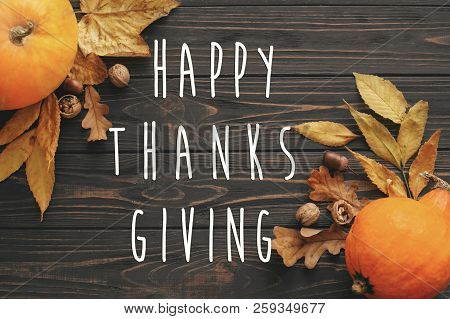 Happy Thanksgiving Text On Beautiful Pumpkin With Bright Autumn Leaves, Acorns, Nuts On Wooden Rusti