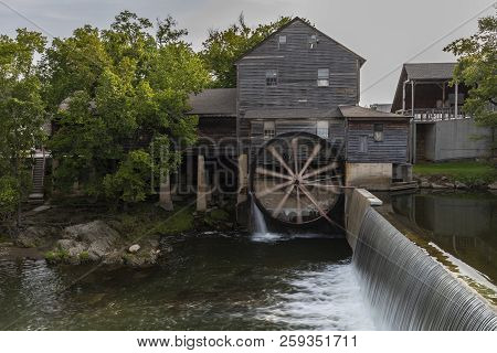 An Old Grist Mill With Water Wheel And Dam.