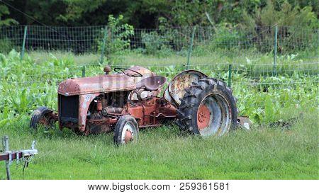 A Rusty Tractor Sits Near A Garden Plot.