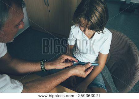 Top View Of A Doctor Is Helping A Diabetic Child To Use An Insulin Pen In His Office. Child Diabetes