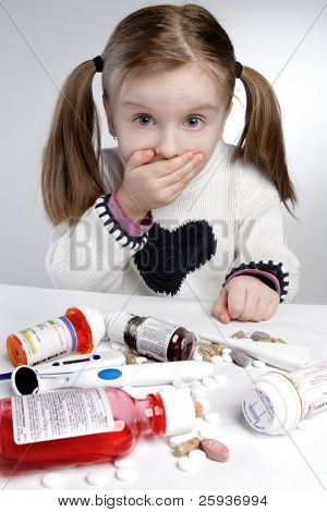 Confused little girl behind pile of medications.