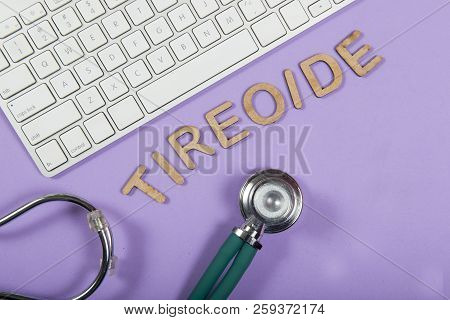 Keyboard And Stethoscope On Lilac Background, With The Word Thyroid (tireoide)