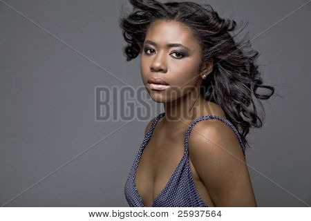 Beautiful young African-American fashion model in blue dress, with hair fluttering on wind.