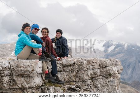 Four Young Male And Female Hikers Sitting On A Mountain Peak Ledge In The Dolomites And Looking At T