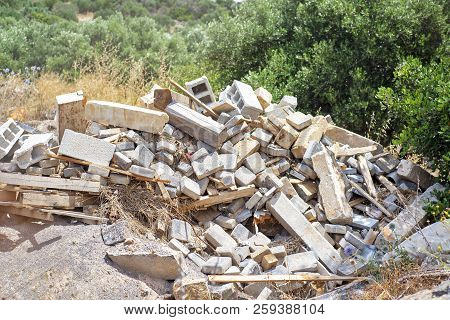 Construction And Demolition Debris. Background Of Olive Trees In Summer.