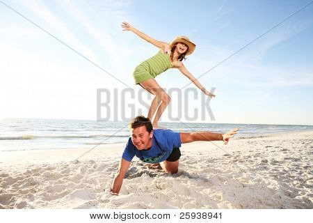 Father and daughter  playing at the summer beach. Shoot against the sun.