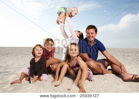 Hermosa familia disfrutando día soleado en la playa.