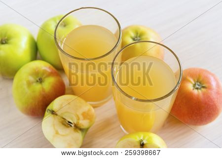 Two Glasses Of Juice, Apple Juice, Whole Apples And Apples Cut In Half,  2 Glasses  Drink