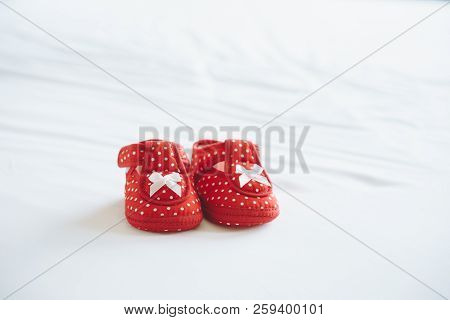Little Baby Shoes On White Bedspread.my First Pair Of Shoes Concept