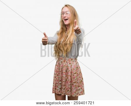 Blonde teenager woman wearing flowers skirt approving doing positive gesture with hand, thumbs up smiling and happy for success. Looking at the camera, winner gesture.