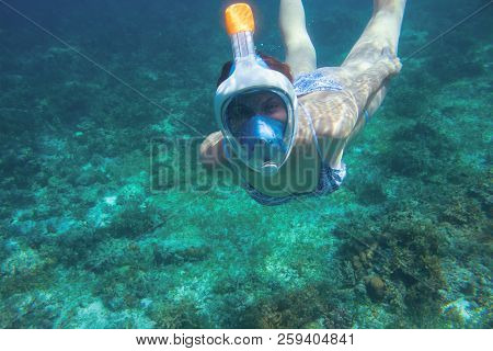 Snorkeling Girl In Swimsuit. Snorkel In Coral Reef Of Tropical Sea. Full-face Snorkeling Mask. Under
