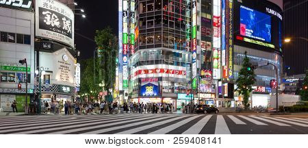 Tokyo, Japan - 19th June 2016: People waiting to cross the street in Shinjuku, downtown Tokyo. This is a busy night spot with plenty of bars, restaurants, shopping and late night entertainment.