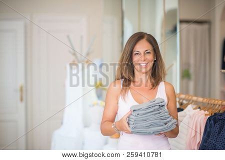 Beautiful middle age hispanic woman standing with smile on face at clothes store. Shop owner and shop assistant smiling confident and cheerful holding clothes.