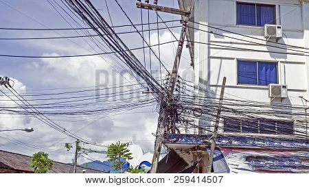 The Chaos Of Cables And Wires On Every Street In Thailand.  Messy Wires Attached To The Electric Pol