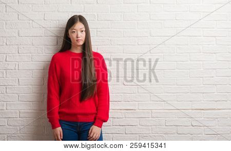 Young Chinese woman over brick wall with serious expression on face. Simple and natural looking at the camera.