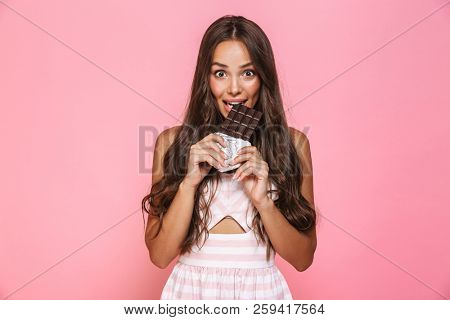 Photo of lovely woman 20s wearing dress smiling and eating chocolate bar isolated over pink background poster