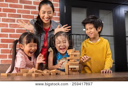 Happy Asian Kids And Their Teacher Are Playing Wooden Blocks Stack Game In Classroom At The School T