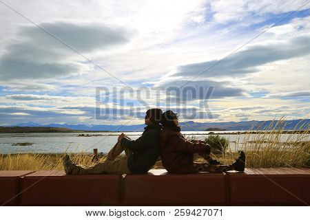 Couple Enjoy The Warm Sunlight Together By The Lake Shore Of Lake Argentino In El Calafate, Patagoni