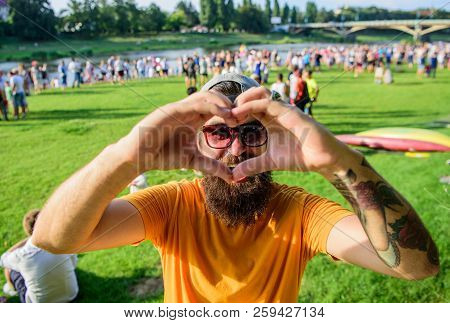 Man Bearded Hipster In Front Of Crowd People Show Heart Gesture Riverside Background. I Love Summer
