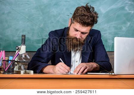 Teacher Bearded Man Writing With Pen Busy With Paperwork. Teacher Formal Jacket Sit Table Classroom