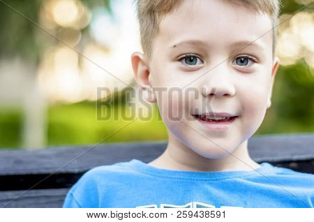Cute Positive Pre-school Age Caucasian Child Smiling, Sitting On The Bench In The Public Park.