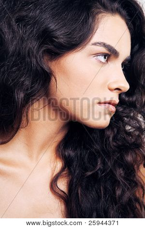 Young beautiful woman with long black curly hair.