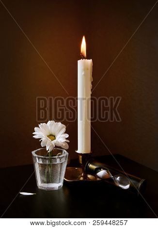 Still Life With White Daisy Flower In The Small Vintage Glass Vase, Sandglass And Burning Candle Aga