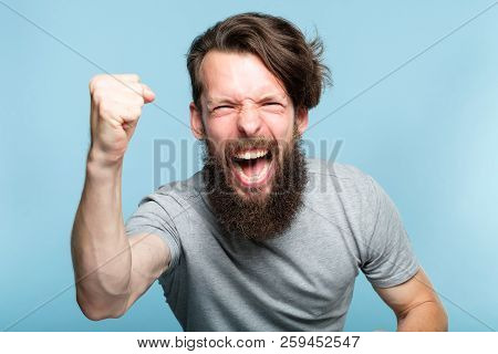 victory success and achievement. excited thrilled agitated guy making a win gesture. hipster man portrait on blue background. emotional reaction and facial expression concept. poster