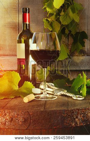 Red wine bottle and glass and grapevine leaves