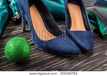 Close Up View Of Bright Feminine Blue Shoes And Green Chirstmas Ball On Wooden Surface