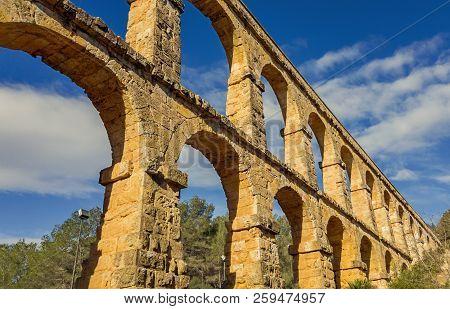 Arches Of The Old Stone Roman Aqueduct In Tarragona, Catalonia, Spain.