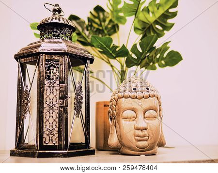 Buddah Statue In Modern Home, Home Decoration. Candle Lighter And Buddha Head Statue And Monstera's