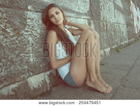 Portrait Of Sexy  Slender Young Woman In White T-shirt, Denim Shorts, Sitting Near Wall In An Erotic