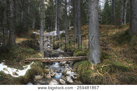 Picturesque Landscape With A Small Alpine River And A Rustic Wooden Bridge, In The Forests Of Alps M