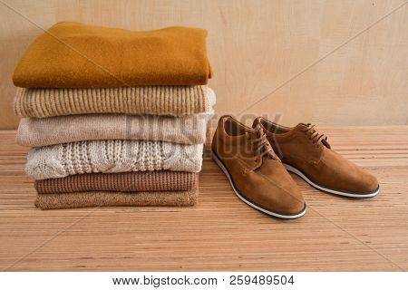 Stack of knitted sweaters with  brown shoes -wooden background