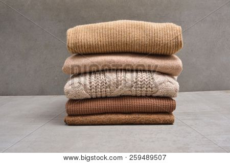 Stack of knitted sweaters-gray background
