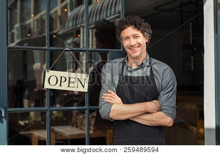 Portrait of small business owner smiling and standing with crossed arms outside the cafe. Portrait of handsome mature waiter standing in entrance of coffee shop.